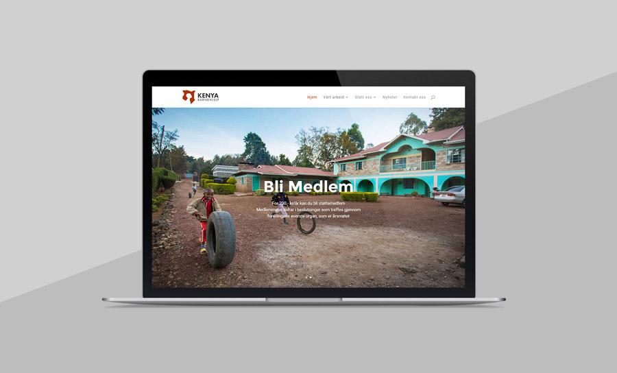 Nettsiden til Kenya Barnehjelp, vist på en macbook med grå bakgrunn